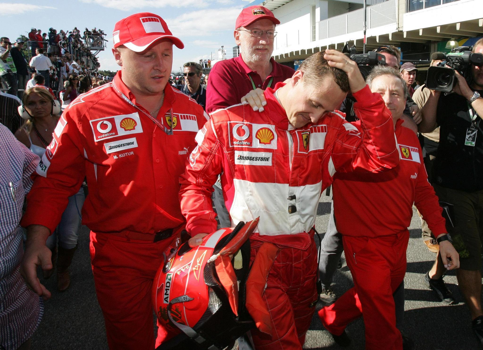 Michael Schumacher walks with Ferrari teammates in the pits