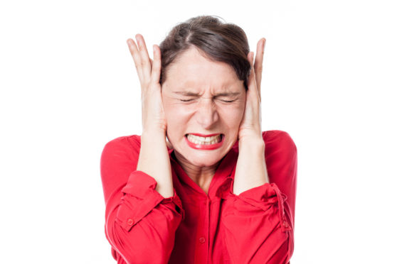 A woman covering her ears because of a loud noise.