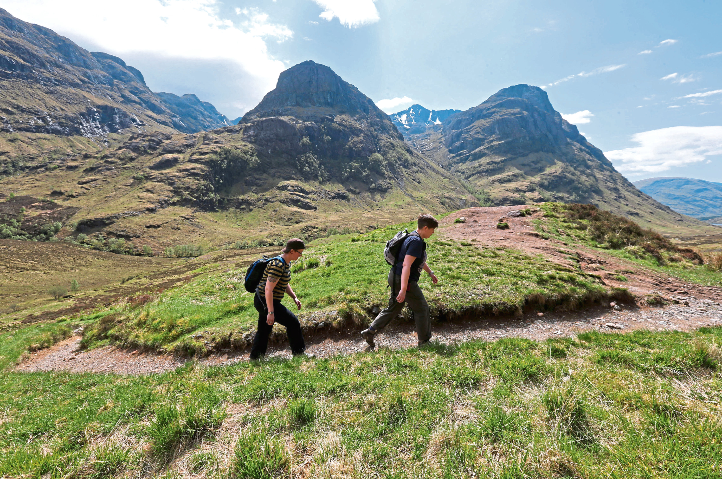 Walkers near the Three Sisters mountain range in the Highlands.