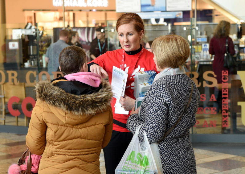 A fundraiser speaking to members of the public  at Union Square, Aberdeen.