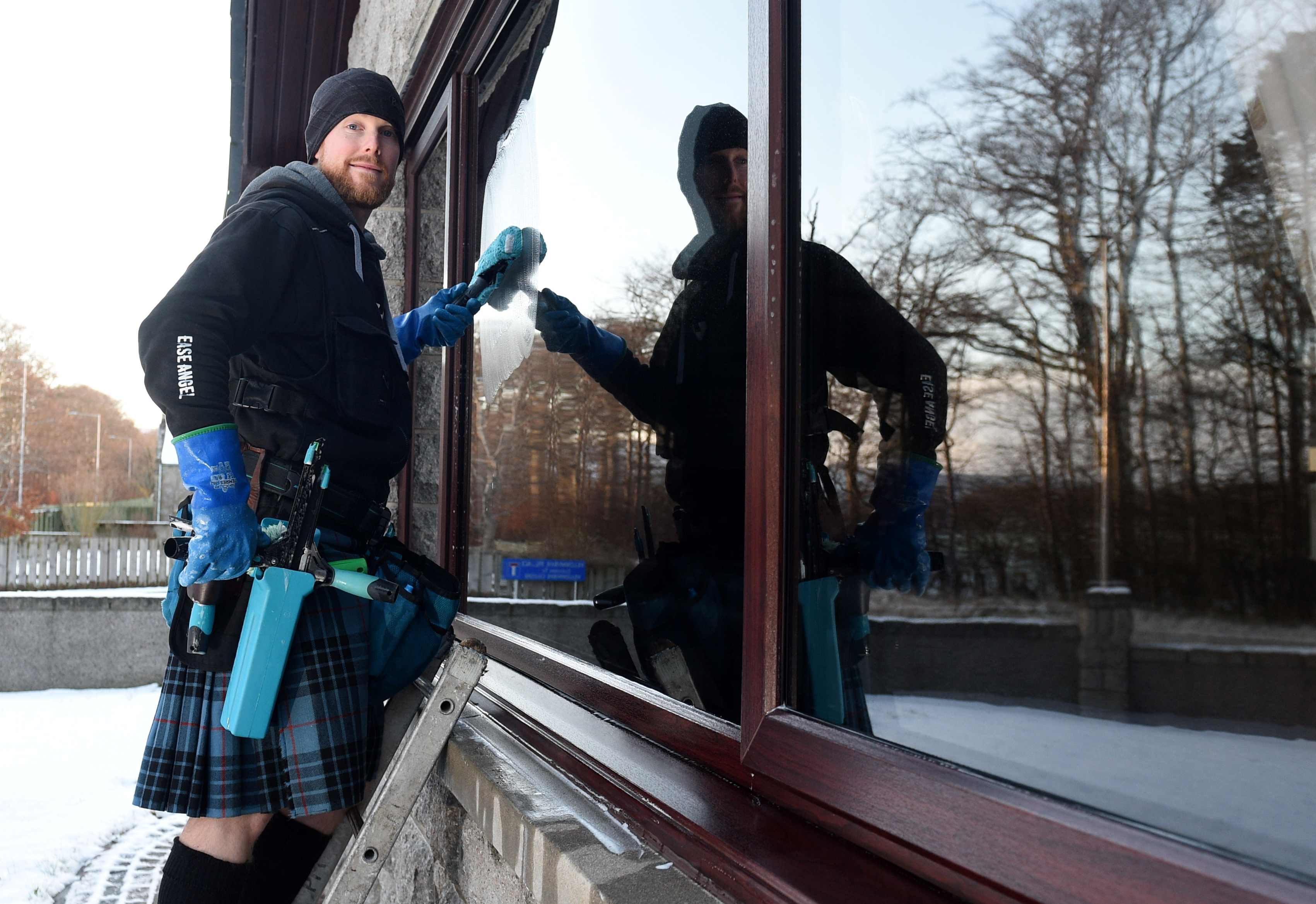 Pictured is Peter McKay washing a window. Peter is a window cleaner and has been wearing a kilt for the best part of a year to raise money for disabled friend and a spinal charity. Pictured on 17/01/2019 Picture by Darrell Benns