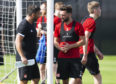 Aberdeen manager Derek McInnes speaks to Graeme Shinnie at training in Dubai.
