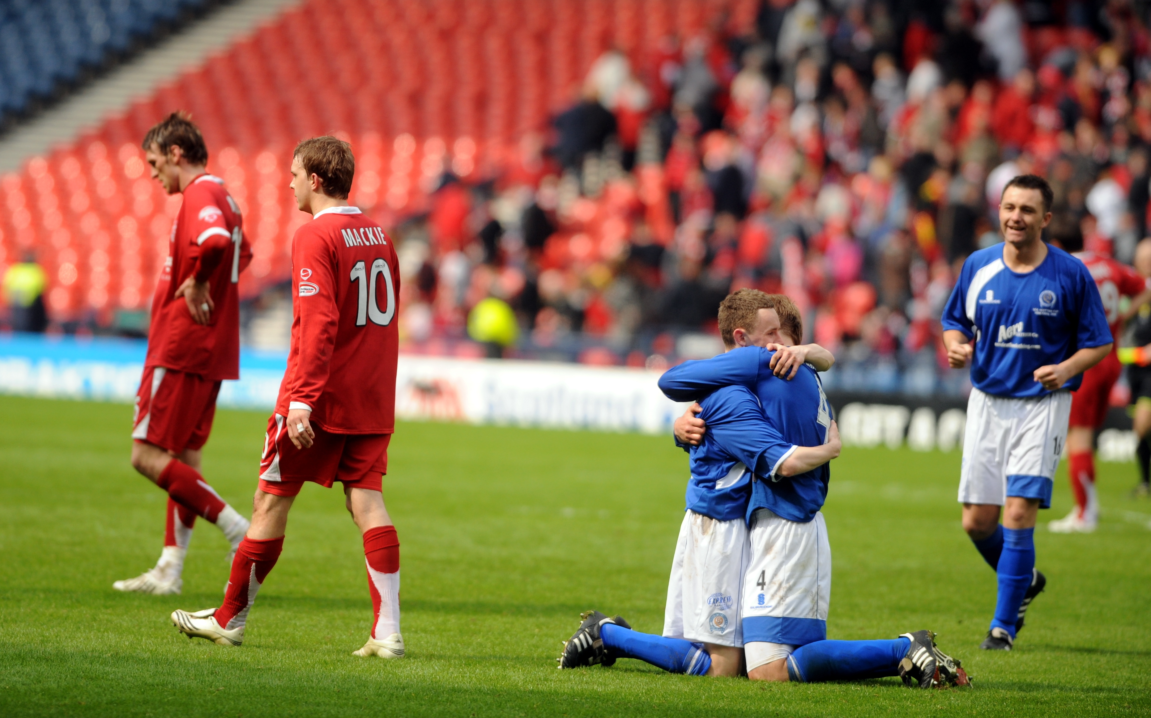 Aberdeen player Darren Mackie walks to the dugout as the Queen of the South players celebrate.