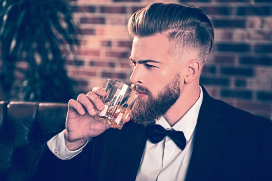 Side half-faced view portrait of masculine serious focused intelligent classy posh modern rich wealthy with trendy hairdo freelancer drinking expensive aged alcohol beverage brick wall is  background