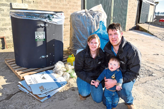 Graham and Ashleigh Thompson, and son Charlie, with the recycling bin they are marketing and some of the items which are collected and baled.