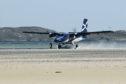 Loganair plane landing at Barra Airport