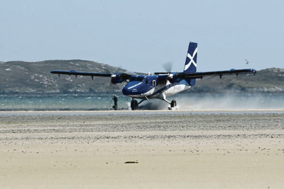 Loganair plane landing at Barra Airport