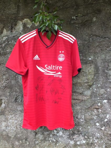 An Aberdeen man is auctioning a signed Dons shirt to help the ARI Staff Garden project.
