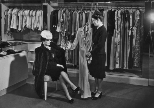 A woman dressed in a fur coat and feathered hat is shown a robe by a saleswoman in the lingerie department of a department store in the 1940's. (Photo by Welgos/Archive Photos/Getty Images)