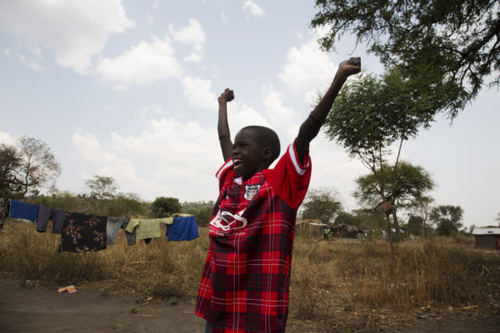 Edea Iren shows off the vintage Fraserburgh FC given to her during a Simon Murphy's trip to Uganda