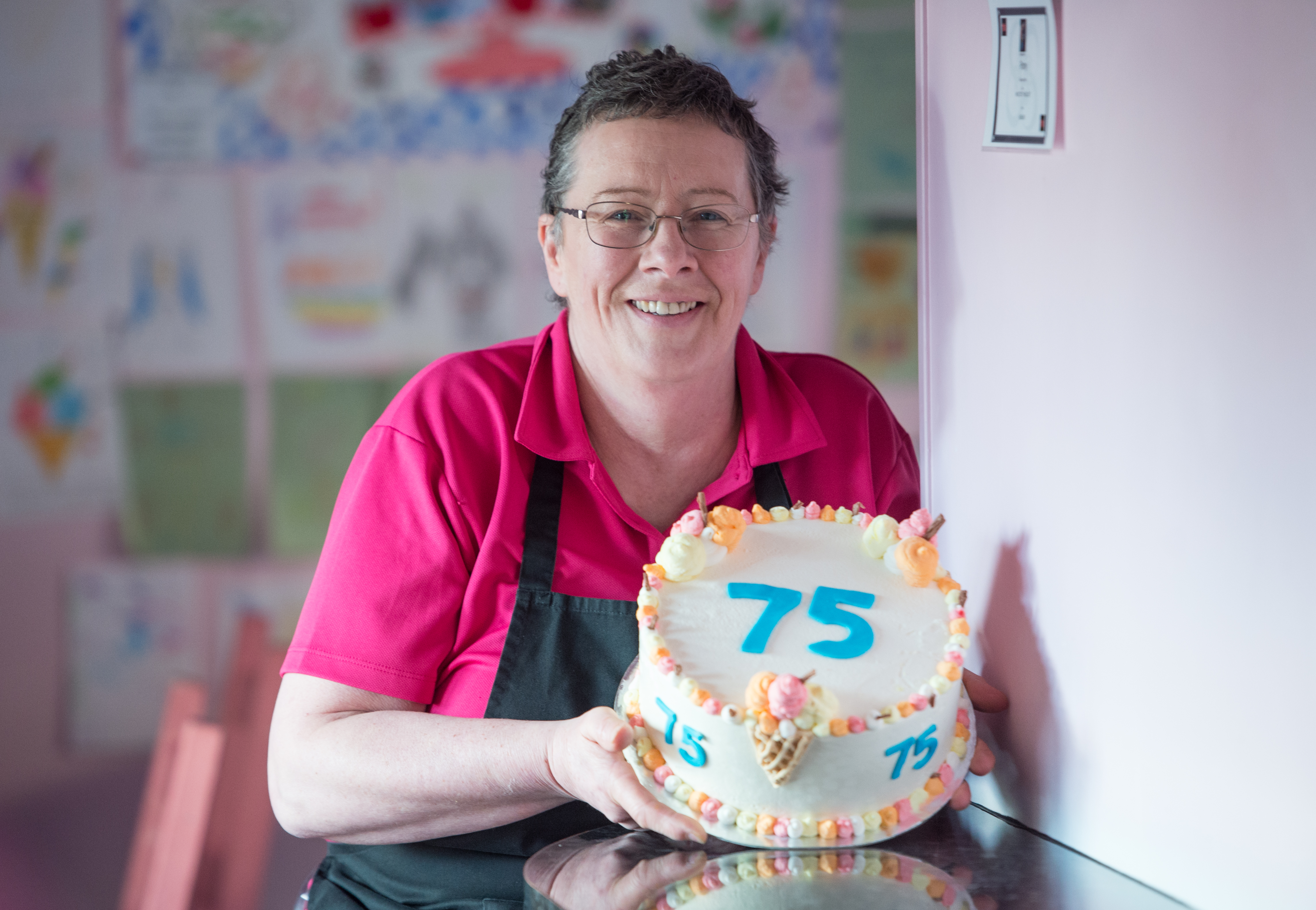 Sheila Gray holding an ice cream cake similar to the won that took a gold award in a National Ice Cream competition.