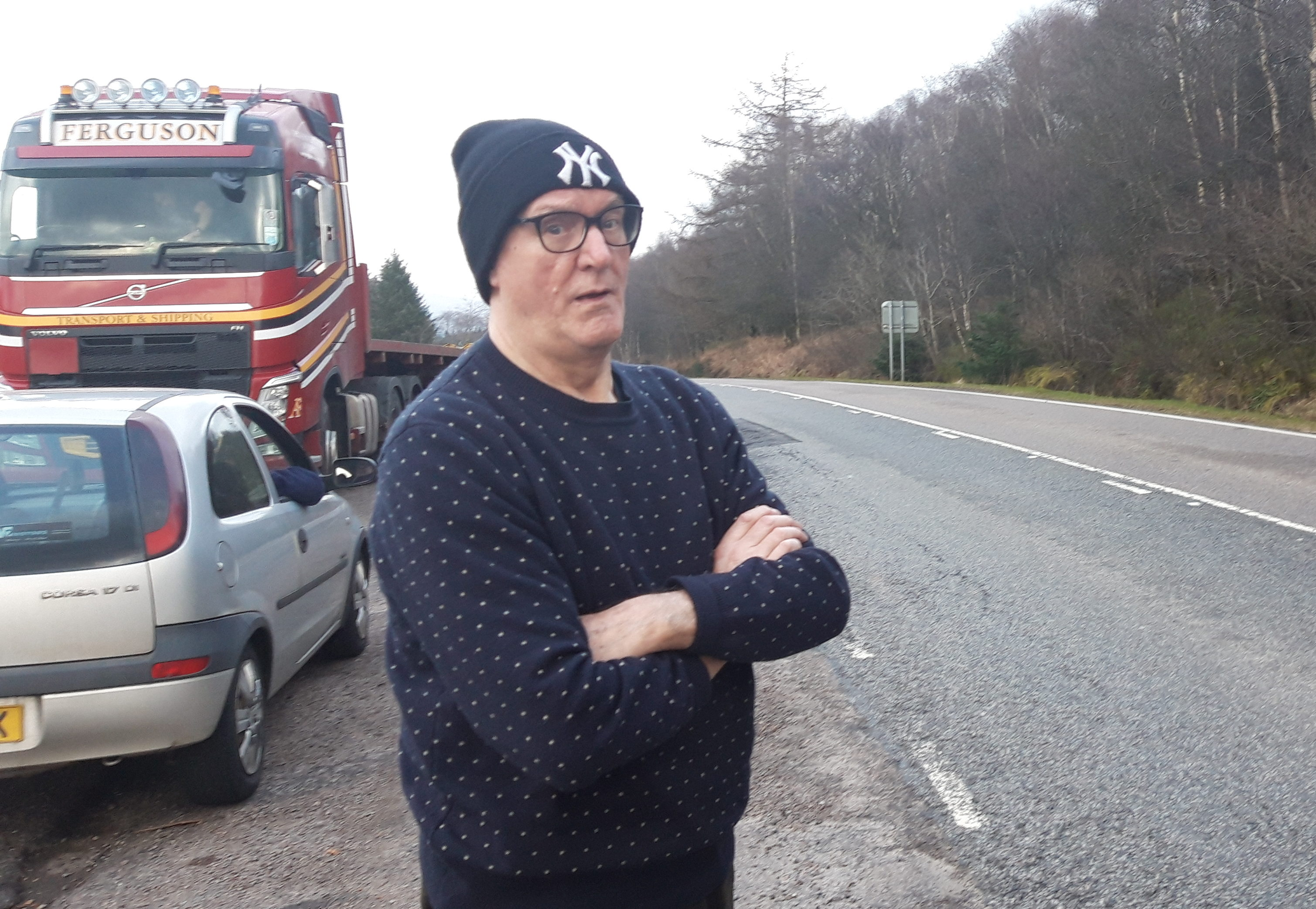 "Phil Walker, near his home on the A82. His car was seriously damaged earlier this month on ""crater"" near to Glencoe."