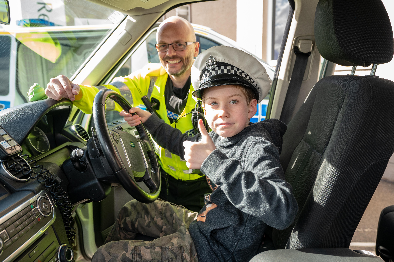 Ben Richards, 10, inside a police car at the Moray Blue Lights Festival.