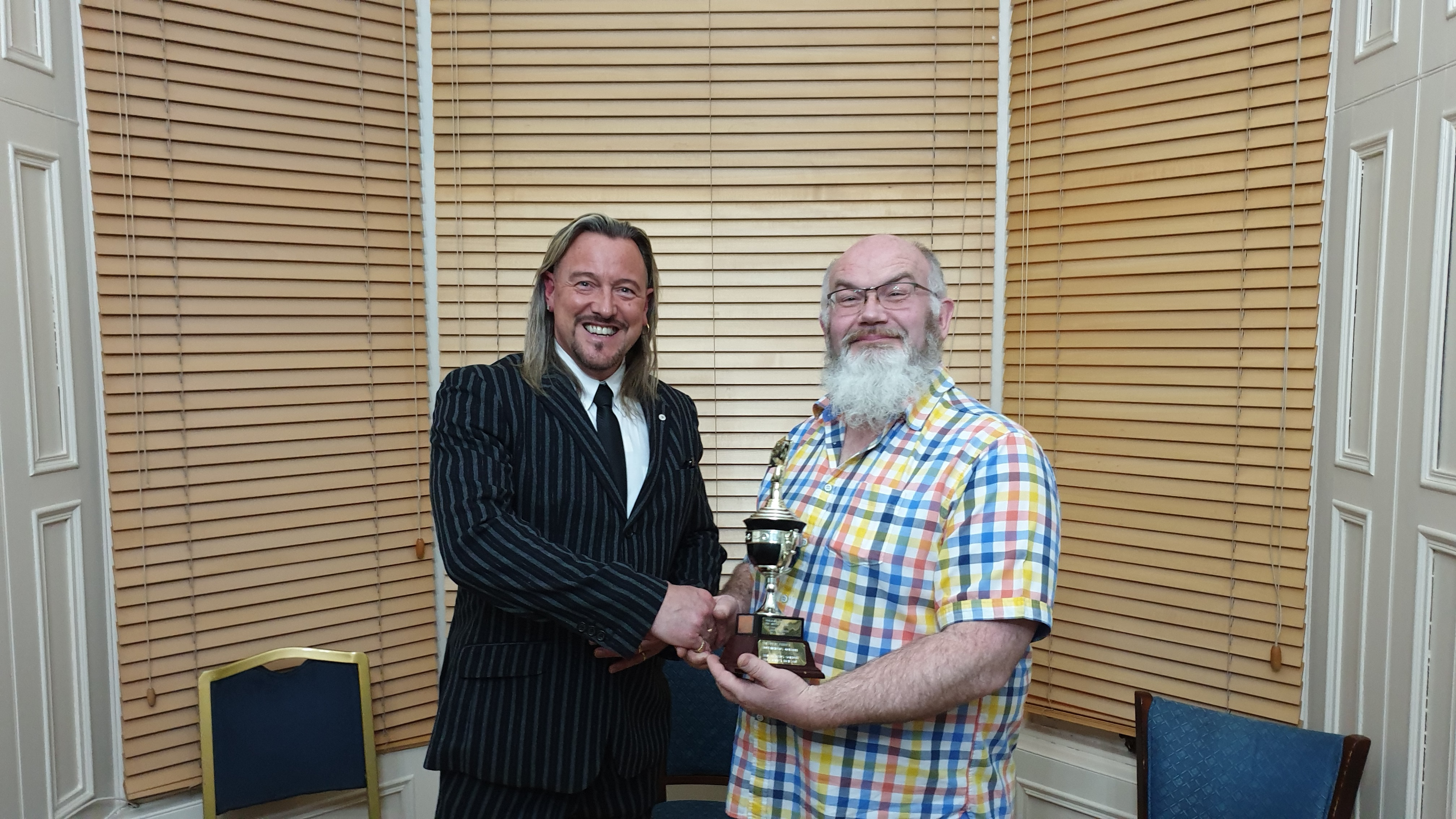 Norn Bichan (right) accepts the Ron Gordon Trophy for Card Magic from Aberdeen Magical Society president Garry Seagraves.