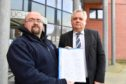 Gilbert Burnett presents the CCTV petition to Chris White from Aberdeenshire Council