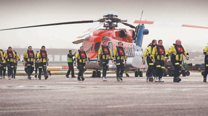 Offshore workers with a CHC helicopter at Aberdeen heliport.