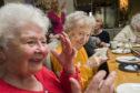 Guests enjoy company at a tea party.