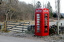 The telephone box now being used as a library which marks one of the diversion routes on the B976.