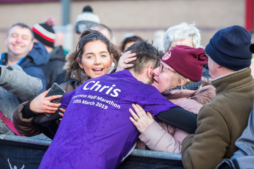 A runner celebrates with an emotional welcome as he finishes the Inverness 1/2 Marathon.