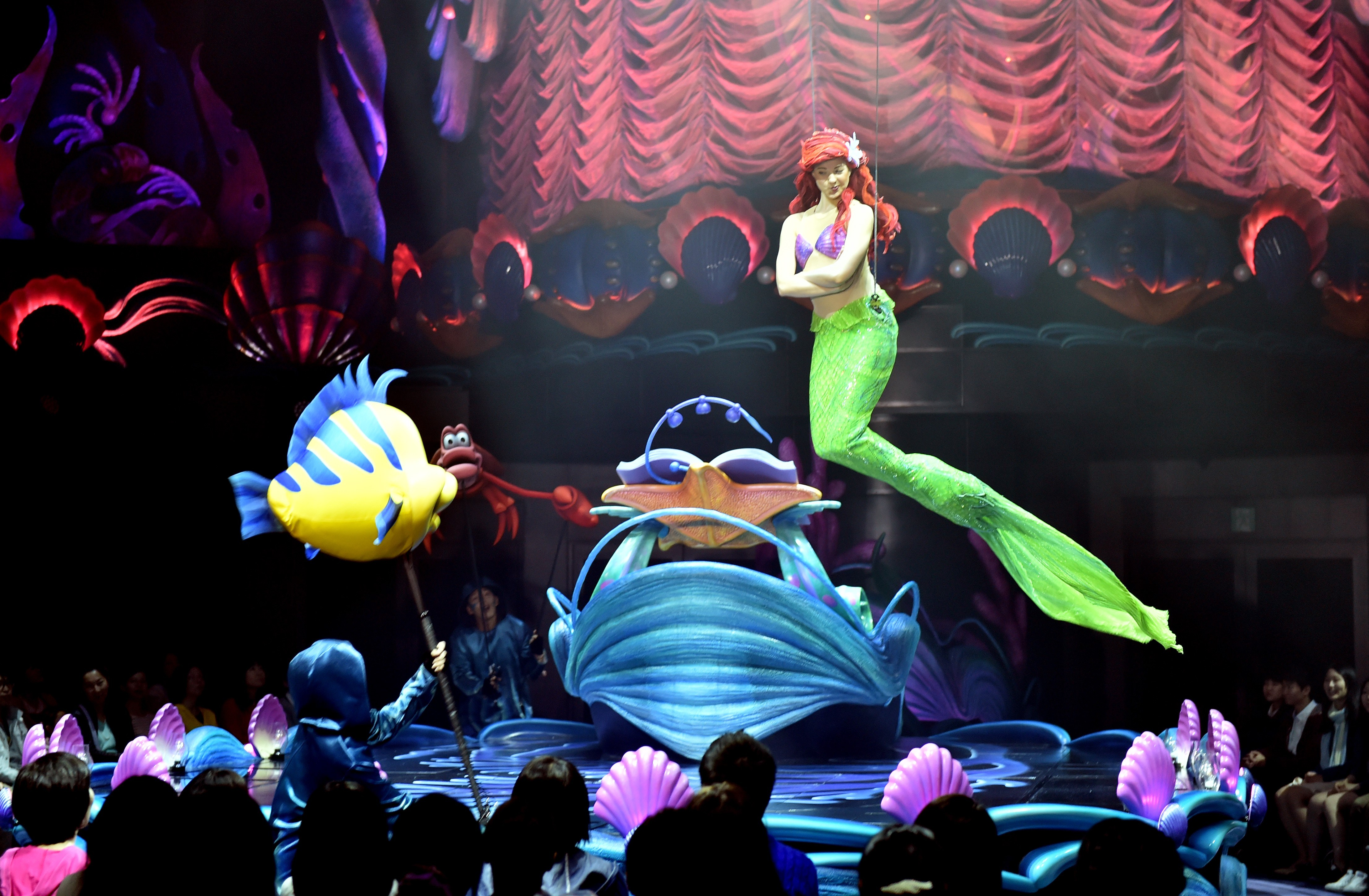 "Disney's Little Mermaid character Ariel sings and displays wire-action performance in the air during the press preview of the new attraction ""King Triton's Concert"" at the Tokyo DisneySea in Urayasu, suburban Tokyo on April 20, 2015. The new musical show will open for public from April 24. Disney theme park Tokyo Disneyland and Tokyo DisneySea marked record high visitors of 31.38 million in the fiscal 2014 year ended March.   AFP PHOTO / Yoshikazu TSUNO        (Photo credit should read YOSHIKAZU TSUNO/AFP/Getty Images)"