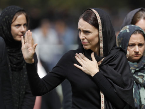 New Zealand Prime Minister Jacinda Ardern, center, waves as she leaves Friday prayers at Hagley Park in Christchurch, New Zealand, Friday, March 22, 2019. People across New Zealand are observing the Muslim call to prayer as the nation reflects on the moment one week ago when 50 people were slaughtered at two mosques. (AP Photo/Vincent Thian)