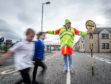 Picture by JASON HEDGES     Stock Images; lollipop man; lollipop lady, school crossing, stop sign; children crossing.  A lollipop person proviodes safe crossings at a road next to New Elgin Primary School in Moray fro children to cross.  Pictures Jason Hedges