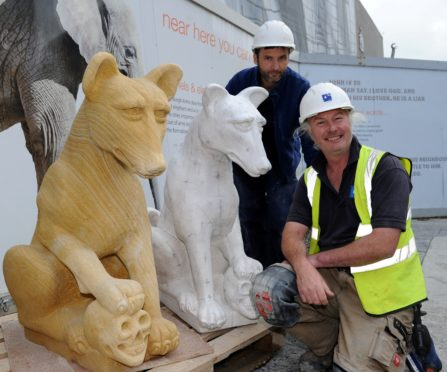 Ivan Navaro and Derek Cunningham, both sculptors and conservators with a model and carved wolf.
