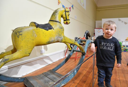 Arbuthnot museum are displaying a collection of vintage toys. Visitor Jack Massie (3) from Aberdeen beside a collection of vintage rocking horses.