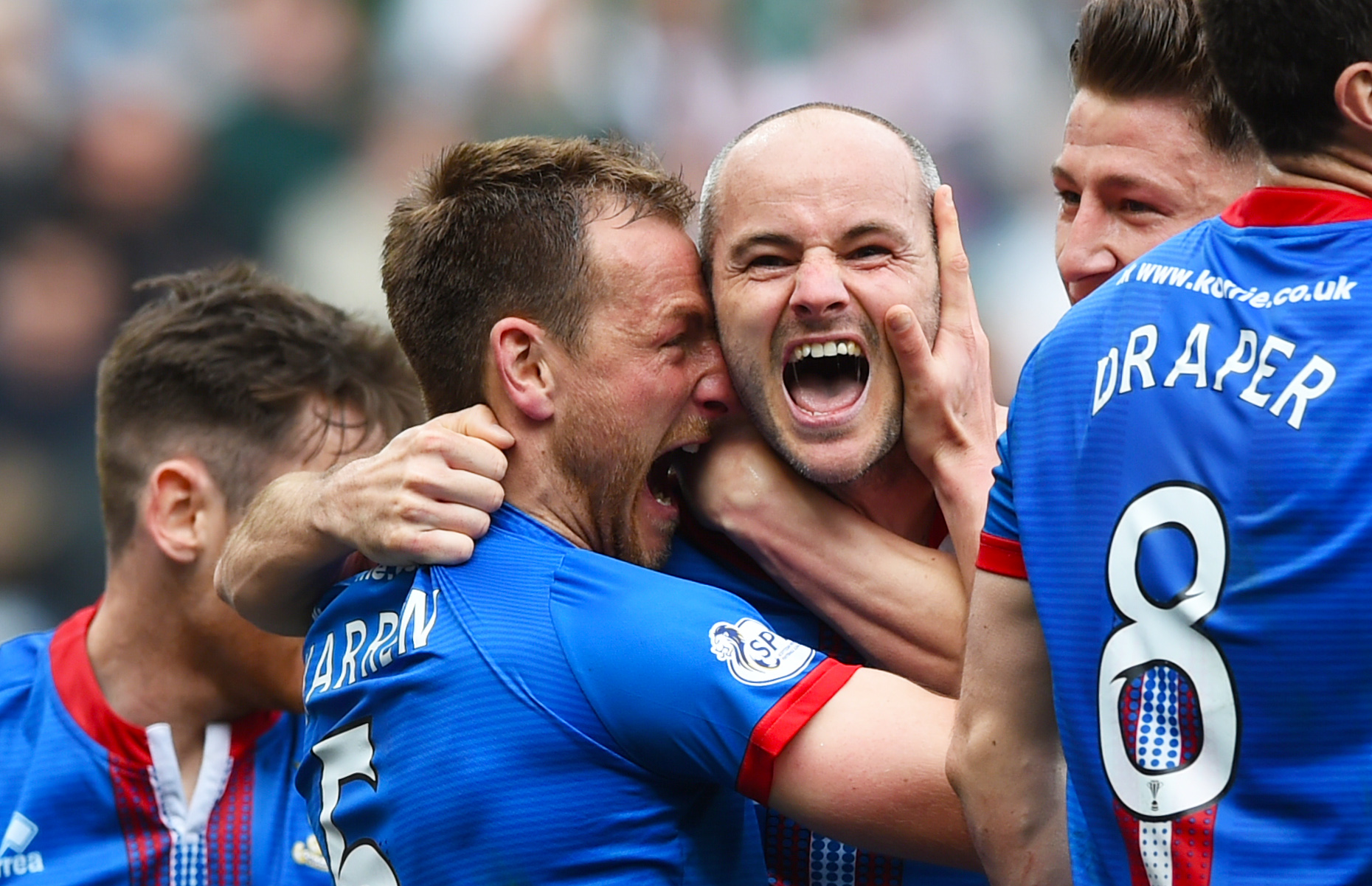 Raven is mobbed by team-mates after his winning goal against Celtic.
