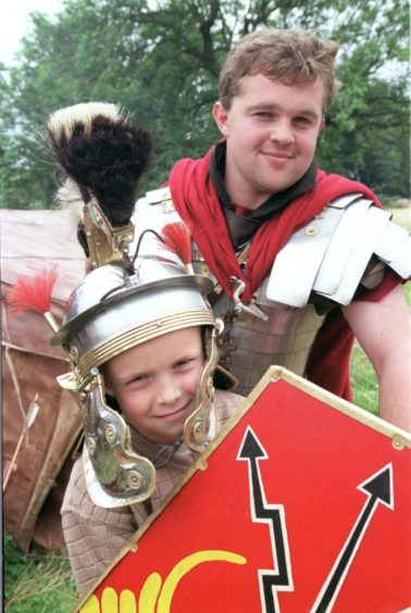 Alex Shepherd (7)  of Roseberry Street,Aberdeen tries on a Centurion's helmet pictured with Nick Backhouse  at Archaeolink,Oyne.