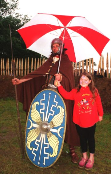 8 Year old Kirsty Perfett from Banchory takes shelter with the help of a Roman solder at Archaeolink Romans and Celtic Weekend.