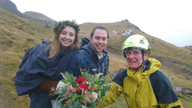 Skye Mountain Rescue Team member Helen Urquhart stops for a moment to have her photo taken with a newly married couple.