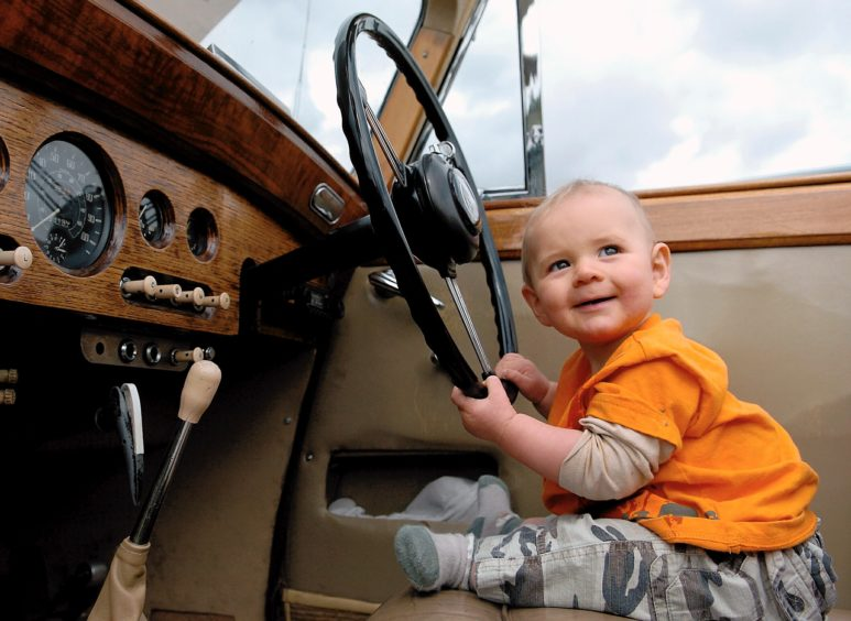 Six month old Cameron Anderson behind the wheel of a classic car. Picture Simon Walton
