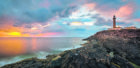 Lighthouse on cliffs of Ardnamurchan Point in colorful sunset,