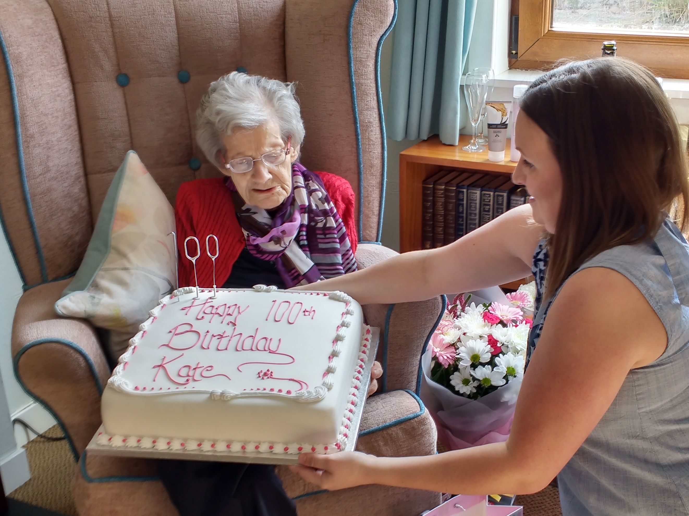 Kate Ingram being presented with her birthday cake by one of her great-nieces Rhona Bowie