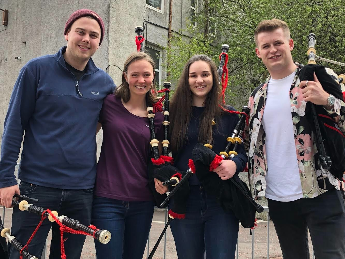Lathallan pupils Lydia Broadley and Rebecca Foster with two members of the Red Hot Chilli Pipers Band