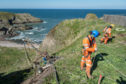Work steps up at Portknockie Harbour to secure any future landslip. Rope access drillers) Kyle Robinson (blue hat) and Josh Mundley (yellow hat). Picture by Jason Hedges