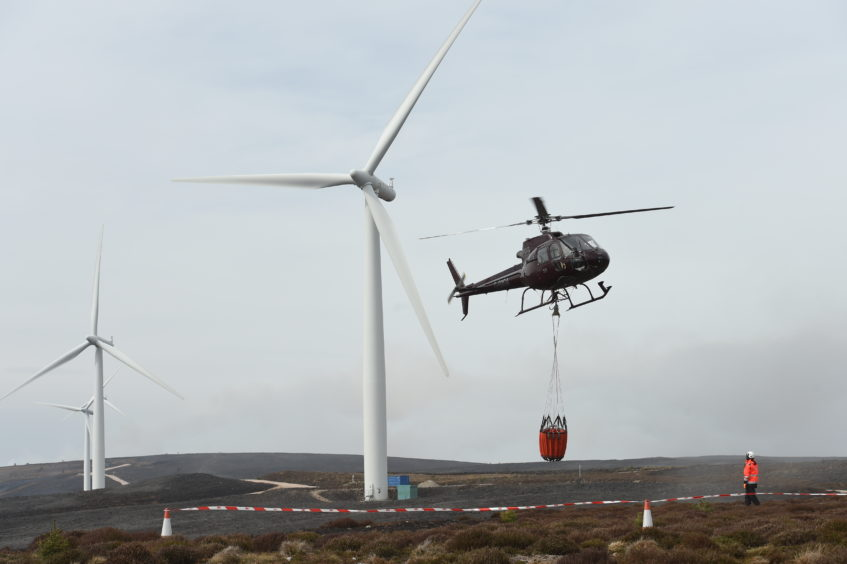 A helicopter sets out to pour water over wildfires in Moray