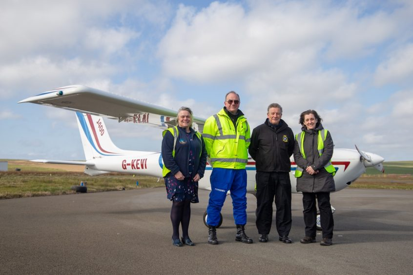 Helen Houston, chair of the Moray Firth Partnership, volunteer Pilots Dave Brown, Paul Horth and Marie Stanton, Highland Park, launch the SCRAPbook coastal mapping in Orkney.