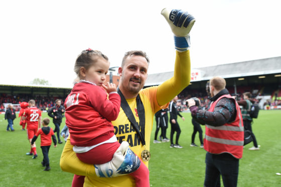 Dean Brill celebrates with his daughter Rosie as Leyton Orient win the Vanarama National League title.