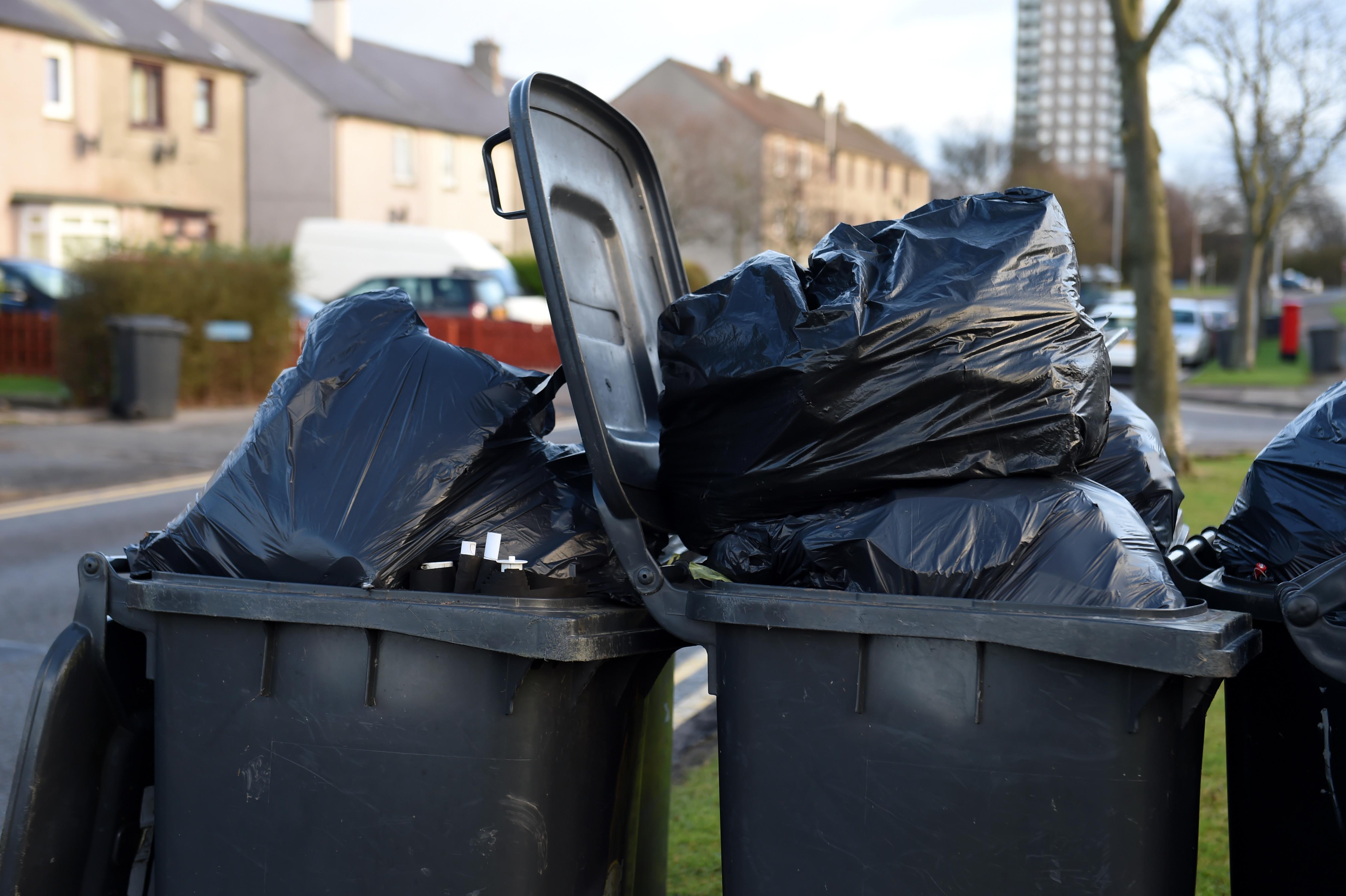 Wheelie bins overflowing with rubbish.