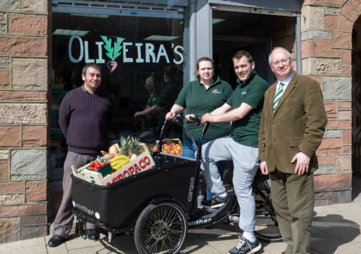 (l-r) Anthony Robertson strategic development officer for Aberdeenshire Council, Cat Henriques De Oliveira, Antero Henriques De Oliveira and Cllr Glenn Reynolds with the Electric cargo bike outside Oliveira's greengrocer in Banff