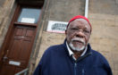 Lansana Bangura, chairman of Elgin Mosque, stands with some of the graffiti.