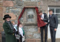 A plaque has been unveiled to remember First World War poet Mary Symon in her Dufftown hometown. Pictured: Lord Lieutenant of Banffshire Clare Russell, Mortlach Primary School pupils Aiden Harvey and Bronagh Gillies and Speyside High School students Andy Milton and Daniel Cotton.