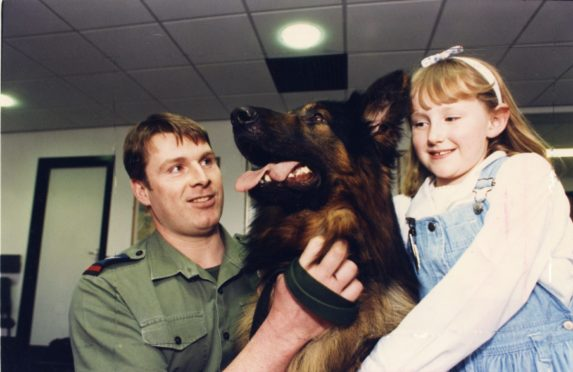 """Dr Gray's Hospital patient Fiona Urquhart, 7 cuddles RAF Police dog Banjo, held by Cpl Ian Booth."""" Picture taken 27 March 1990."""