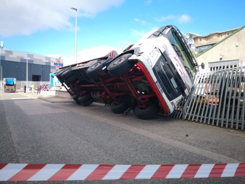 A lorry toppled over during a delivery and pinned a man to a fence.
