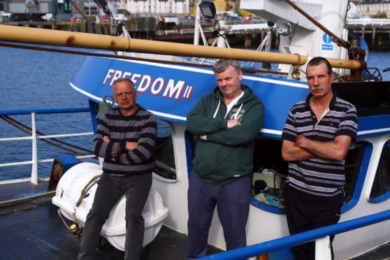 Angry skipper Jonathan MacAllister (centre) with latvian crewmen Guntis Hausmanis (right) and Janis Stals tied up aboard the Freedom losing money waiting for their crewman.