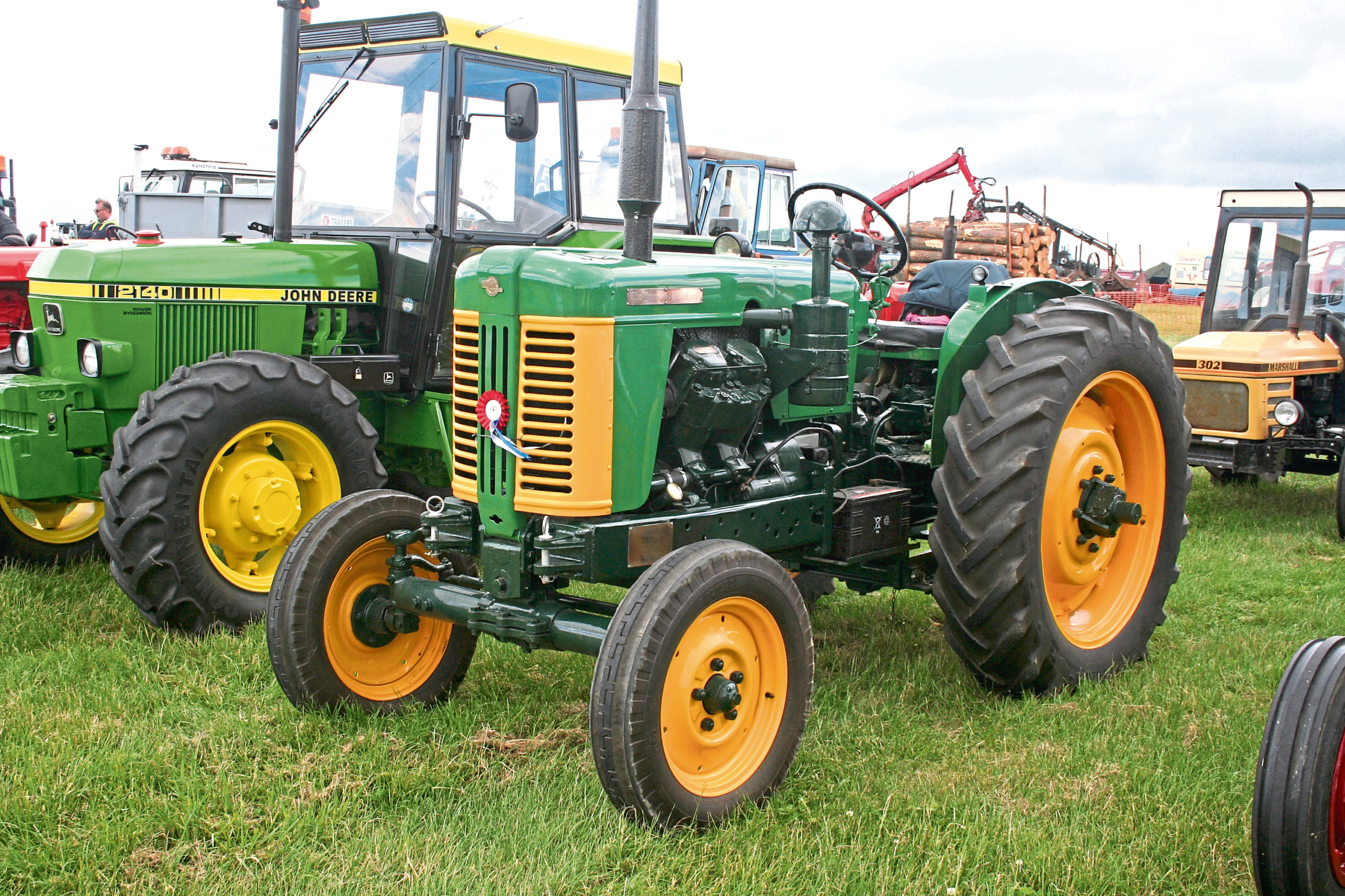 A 1950s Turner Yeoman of England, bearing the distinctive green and yellow colour scheme, stands next to a more modern John Deere model
