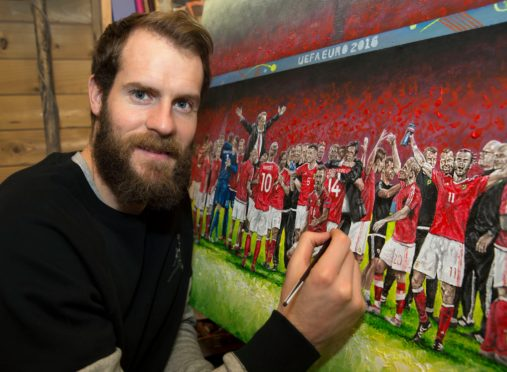 Owain Fon Williams with one of his paintings of the Wales national side.