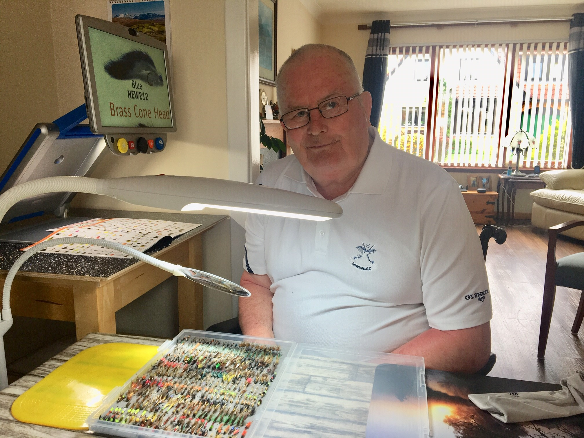 Del Tulloch, 75, of Inverness, with some of his flies; Del pictured with his CCTV and specialist lighting from Scottish War Blinded that he is using to practise tying flies again and read his fishing magazines.​